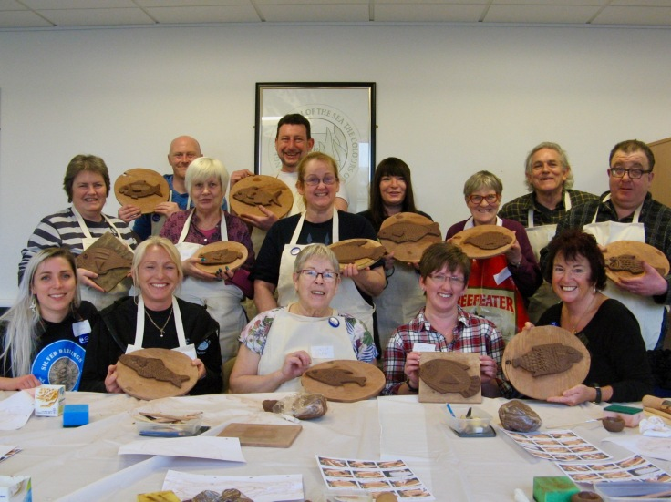 Library workshop members learning texturing, joining whilst making fish.